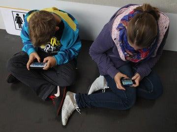Niños consultando el móvil