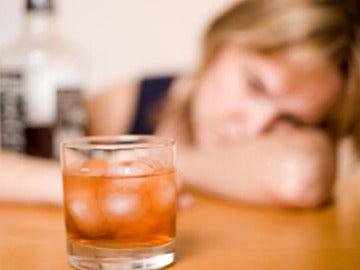 Una mujer ante un vaso con alcohol