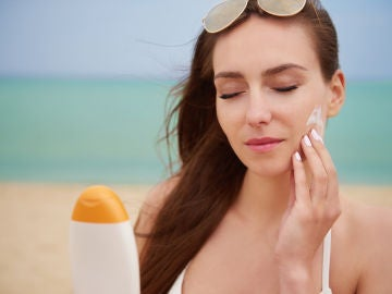 Mujer poniendo crema solar en la cara