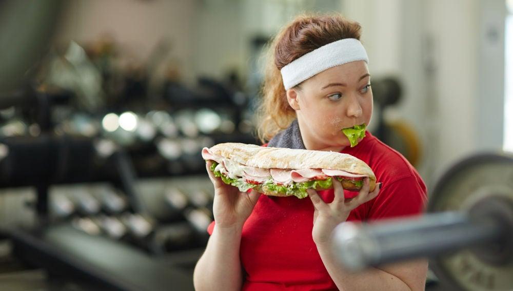 Una chica come un bocadillo enorme en el gimnasio