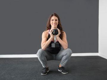 Mujer hace una sentadilla con peso