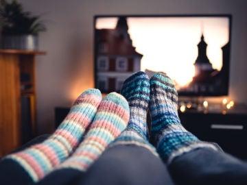 Pareja viendo la tele con calcetines gruesos