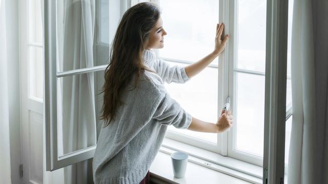 Imagen de archivo de una chica ventilando una habitación.