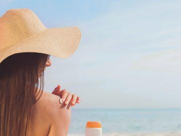 Mujer echándose crema solar en la playa