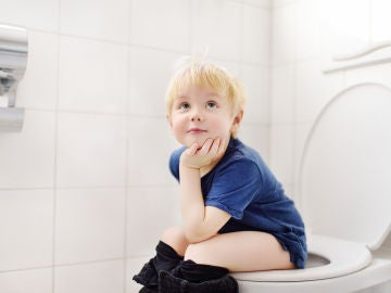 Niño sentado en urinario