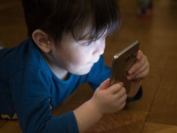Imagen de archivo de un niño usando un teléfono móvil